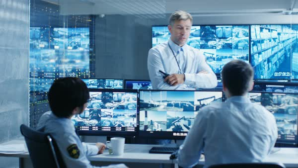 In the Security Control Room Chief Surveillance Officer Holds a Briefing for Two of His Subordinates. Multiple Screens Show that They Guard Object of International Importance.  Royalty-free stock video