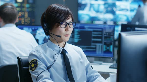 In the Security Command Center Officer at His Workstation Monitors Screens and Communicates with Patrols through Headset. He is Part of the Surveillance Team.  Royalty-free stock video