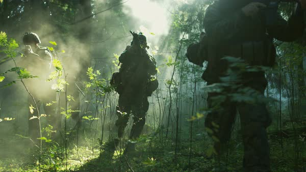Fully equipped soldiers wearing camouflage uniform attacking enemy, rifles ready to shoot. Military operation in action, squad running in formation through dense smokey forest. Following shot.  Royalty-free stock video