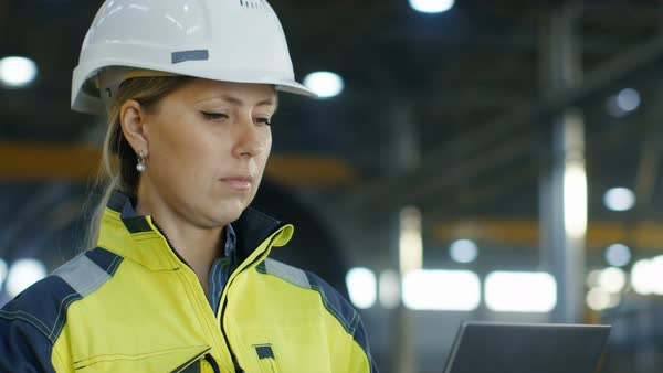 Portrait female industrial engineer in the hard hat uses laptop computer while standing in the heavy industry manufacturing factory Royalty-free stock video