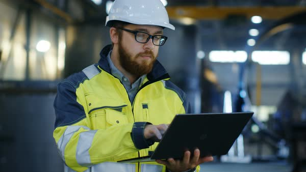 Industrial engineer in hard hat wearing safety jacket uses laptop Royalty-free stock video