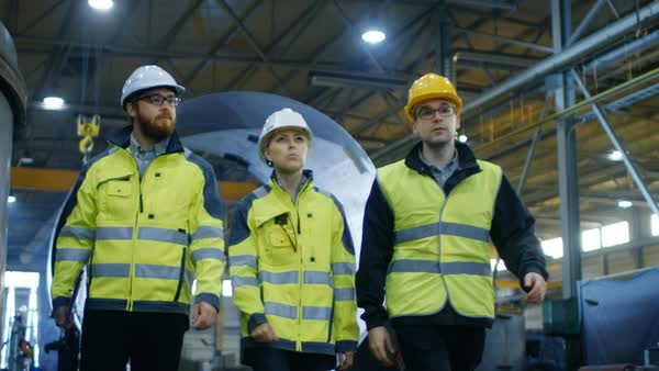 Following shot of three engineers walking through heavy industry manufacturing factory Royalty-free stock video
