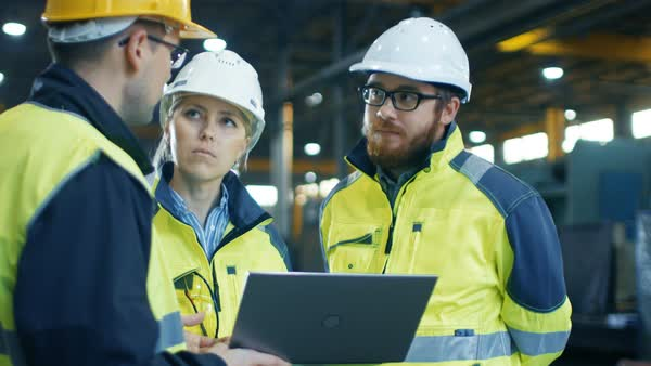 Male and female industrial engineers talk with factory worker while using laptop Royalty-free stock video