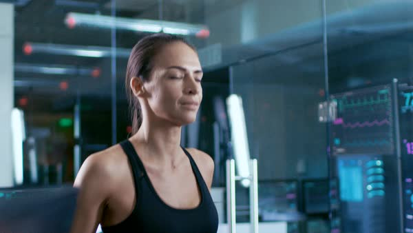 d437571252 In scientific sports laboratory beautiful woman athlete walks on a treadmill  with electrodes attached to her