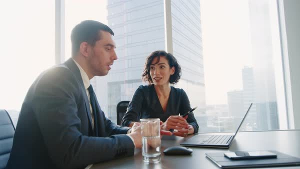 Low Angle Shot Of Confident Businesswoman And Businessman Talking