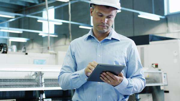 Engineer in hard hat is using tablet pc on factory Royalty-free stock video