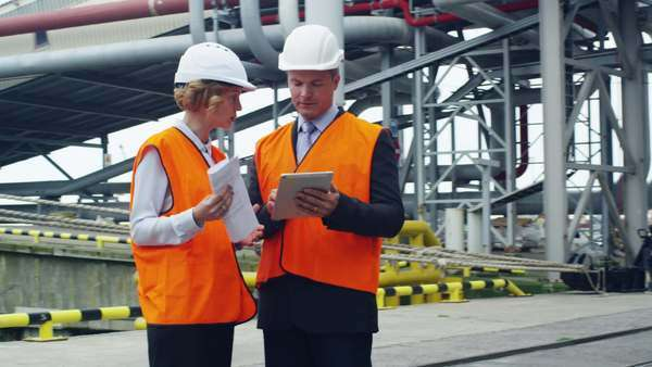 Business people in safety vests using tablet in industrial environment Royalty-free stock video