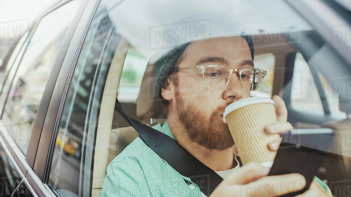 Stylish Young Man Riding in a Car, Sitting on a Passenger Seat Uses Smartphone, types Message, Browses Through Internet, Drinks Coffee. Camera Shot from Outside the Vehicle. Royalty-free stock photo