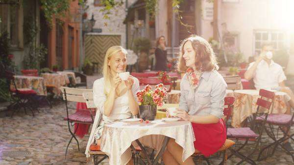 Two girls have conversation in outdoor coffee shop Royalty-free stock video