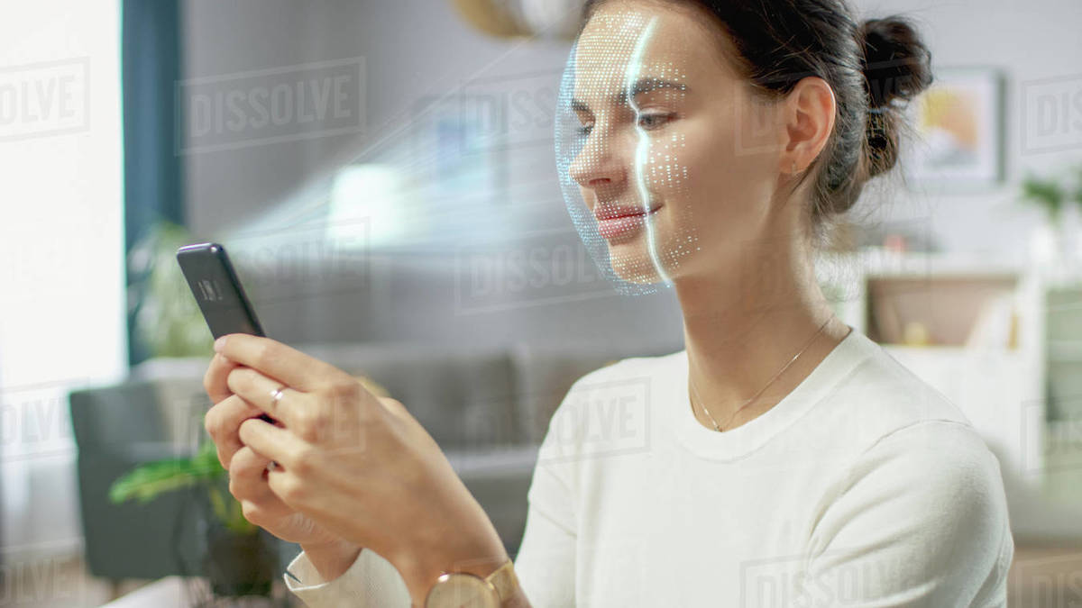 Young female identified by biometric facial recognition scanning process from her smartphone. Futuristic concept: projector identifies individual by illuminating face by dots and scanning with laser Royalty-free stock photo