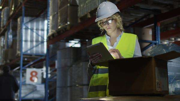 Female manager of logistics warehouse is working on tablet. Wears a white hard hat. Royalty-free stock video