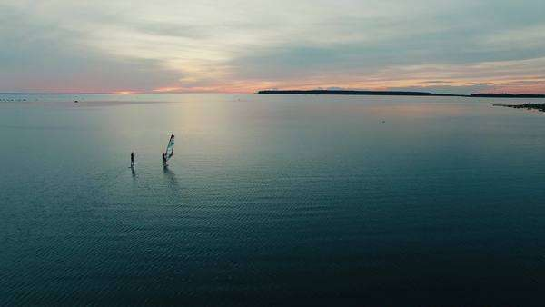 Aerial drone shot of windsurfer and paddleboarder at sunset. Royalty-free stock video
