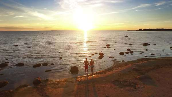 Aerial drone shot of a couple running into water at sunset. Royalty-free stock video