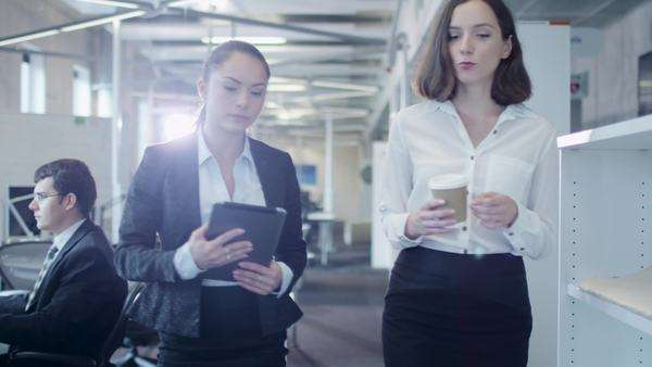 Two attractive female workers are walking through office. One of them holding tablet pc. Royalty-free stock video