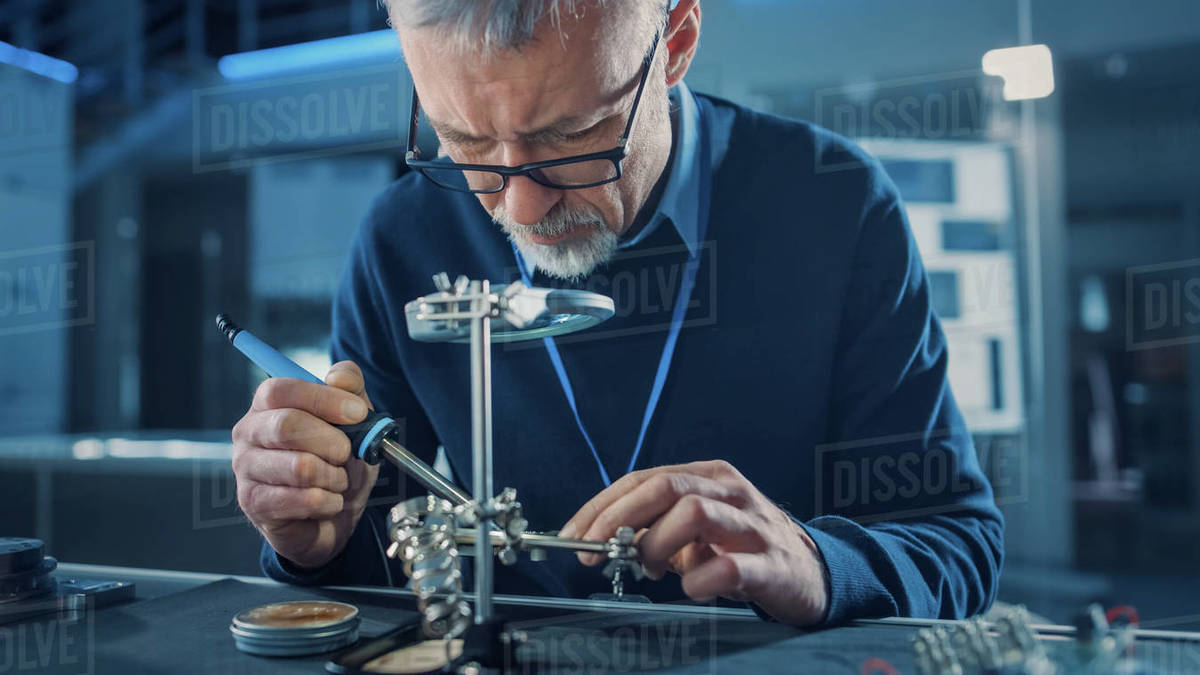 Electronics Maintenance Engineer Soldering Motherboard, Microchip and Circuit Board, Looking through Magnifying Glass, Consults Personal Computer. Electronics Repair and Testing Royalty-free stock photo