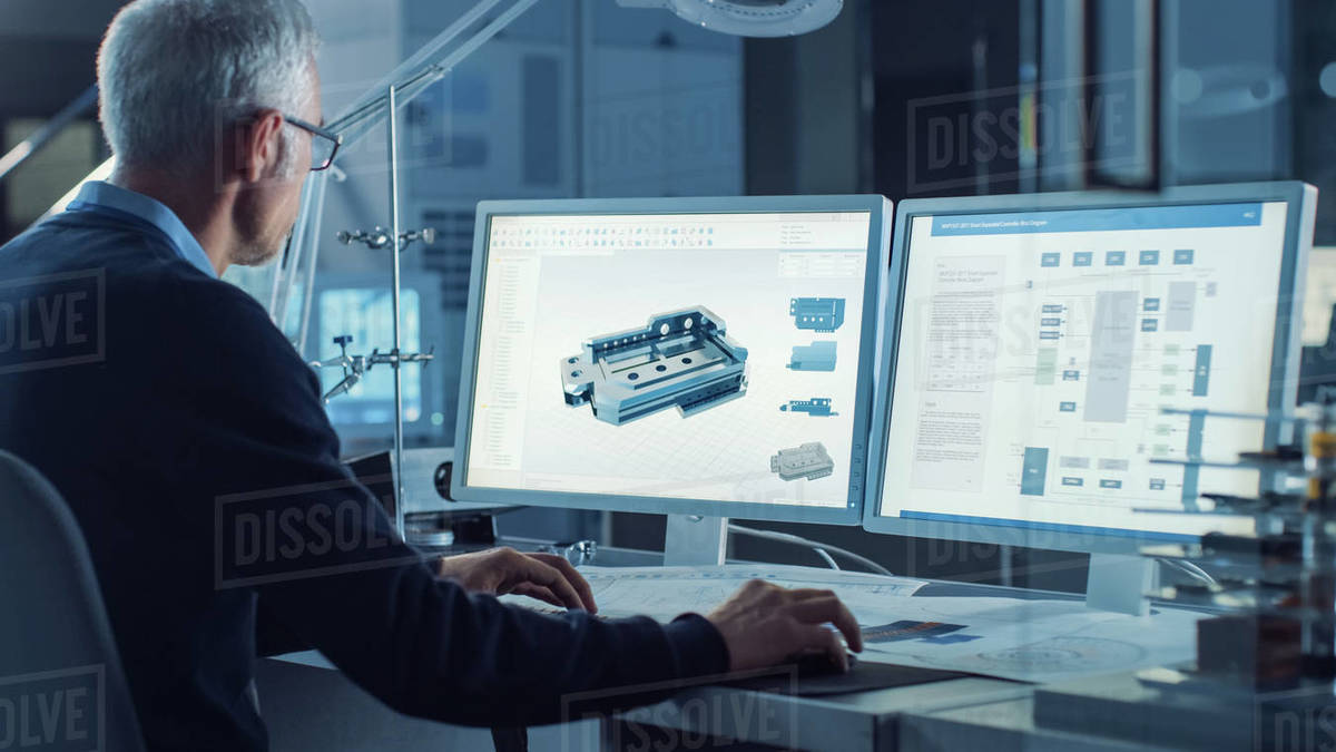 Professional Heavy Industry Engineer Works on Computer Uses CAD Software with Integrated development environment to Design Industrial Machinery Component. Over the Shoulder Shot Royalty-free stock photo