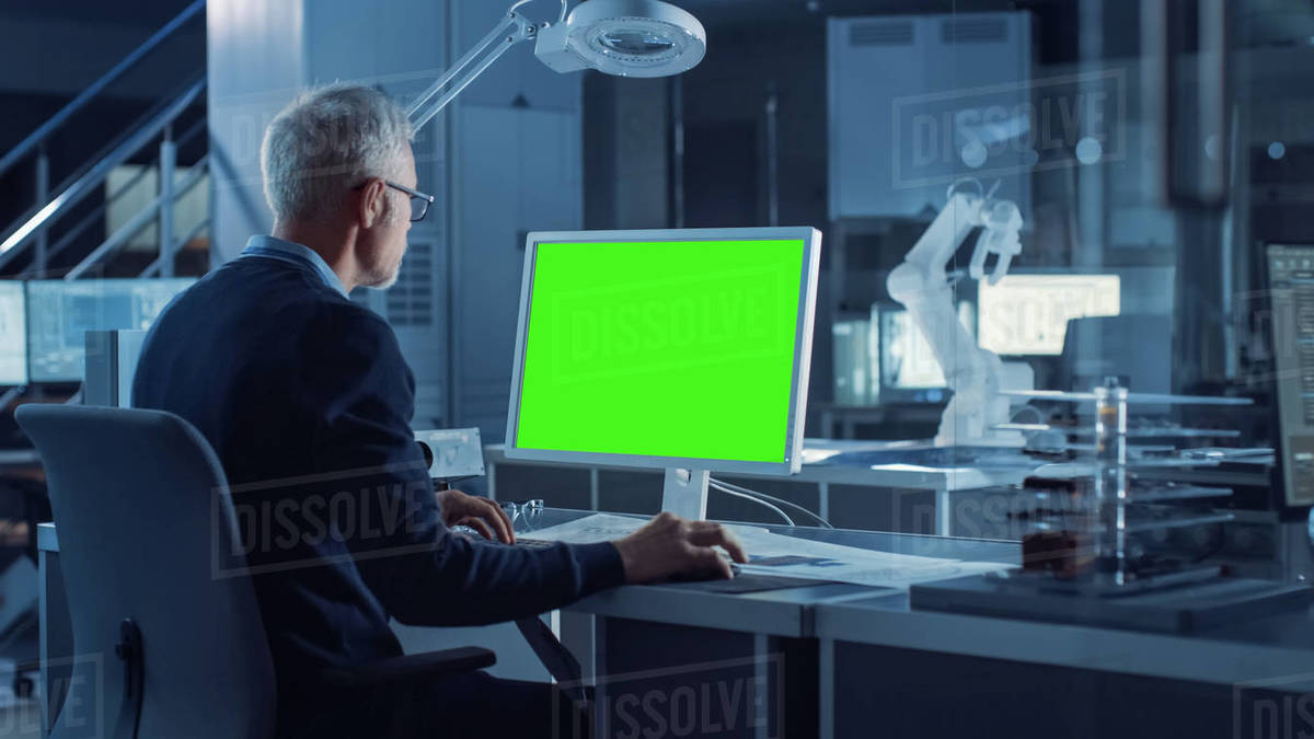 Professional Heavy Industry Engineer Works on Green Mock-up Screen Computer. Engineering Bureau and Industrial Design Agency with Various Robotic, Architectural and Machinery Components Royalty-free stock photo