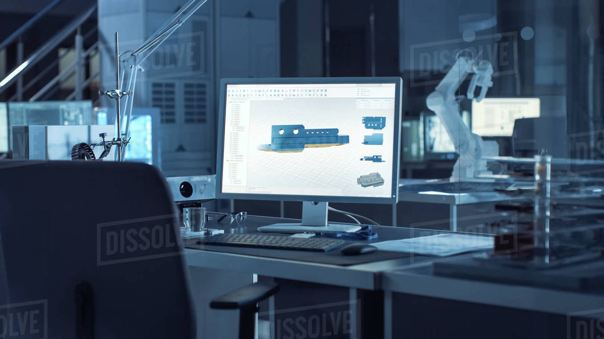 On the Desk Computer With CAD Software and Design of 3D Industrial Machinery Component. In the Background Robot Arm Concept Standing in Heavy the Dark.Industry Engineering Facility. Royalty-free stock photo