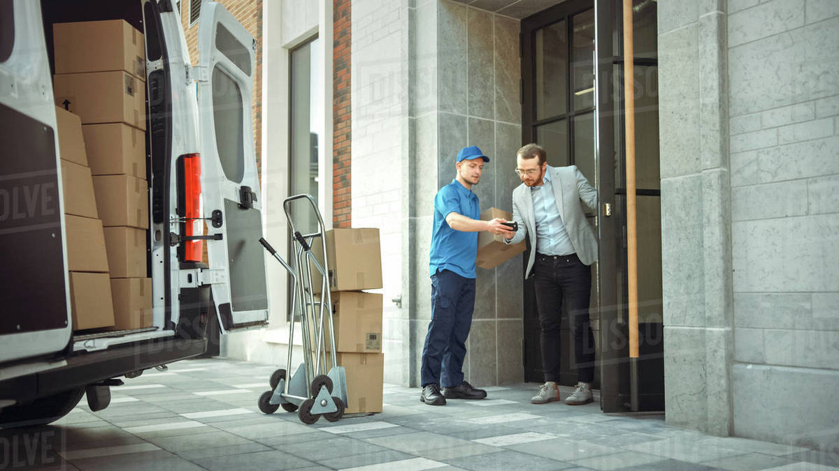 Delivery Man Gives Postal Package to a Business Customer, Who Signs Electronic Signature POD Device. In Stylish Modern Urban Office Area Courier Delivers Cardboard Box Parcel to a Man. Royalty-free stock photo