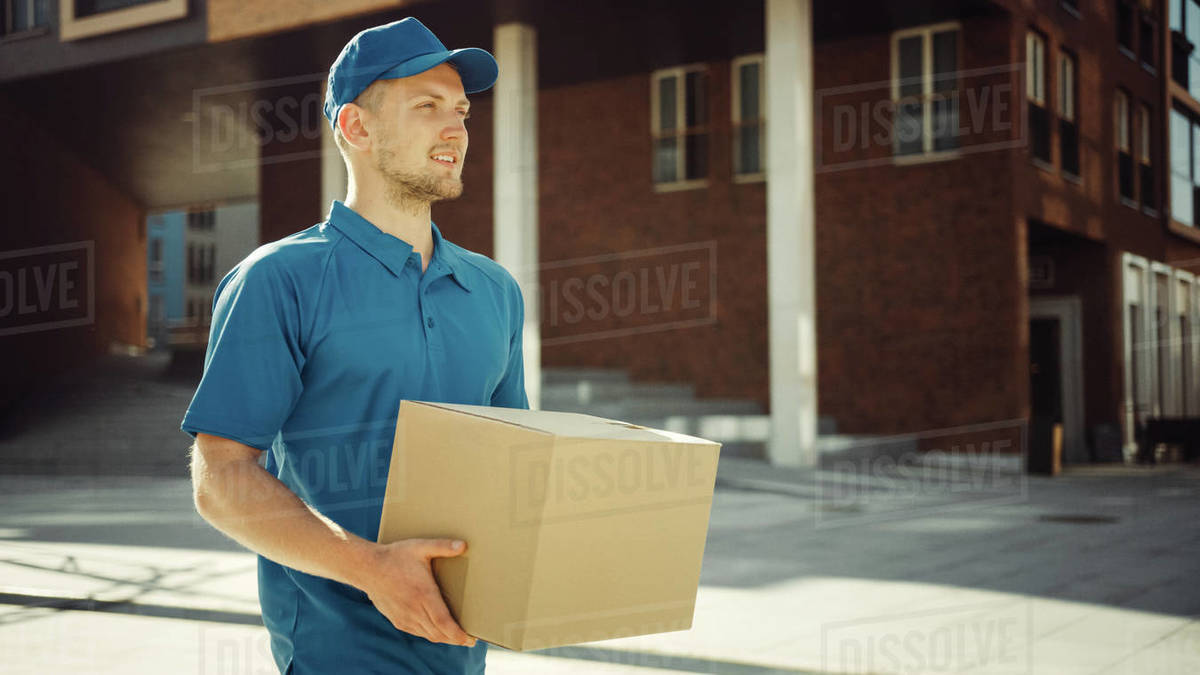 Handsome Delivery Man Holds Cardboard Box Package Walks Through Modern Stylish Business District. Courier On the Way to Deliver Postal Parcel to a Client. Royalty-free stock photo