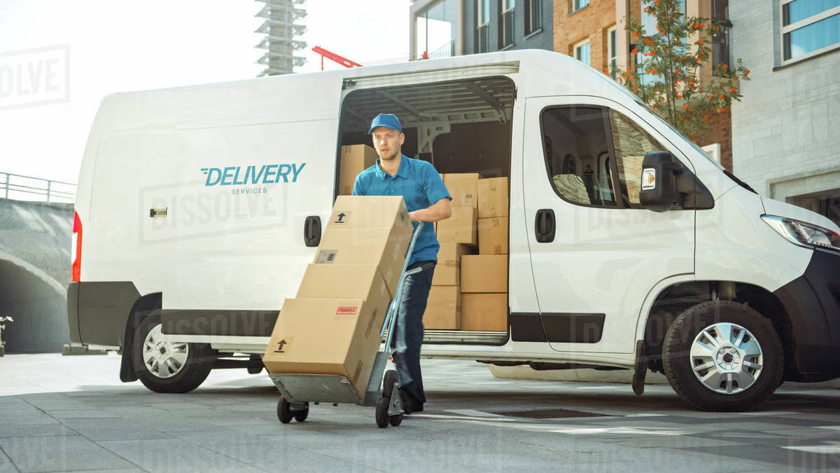 Delivery Man Pushes Hand Truck Trolley Full of Cardboard Boxes Hands Package to a Customer. Courier Delivers Parcel to Man in Business District. Royalty-free stock photo