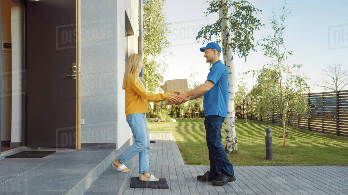 Delivery Man Delivers Cardboard Box Package to a Beautiful Young Woman, Who will Sign Electronic Signature POD Device. In the Background Cute Suburban Neighbourhood. Side View Shot Royalty-free stock photo