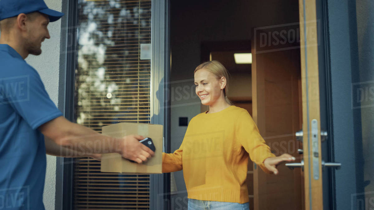 Beautiful Young Woman Opens Doors of Her House and Meets Delivery Man who Gives Her Cardboard Box Postal Package, She Signs Electronic Signature POD Device. Royalty-free stock photo