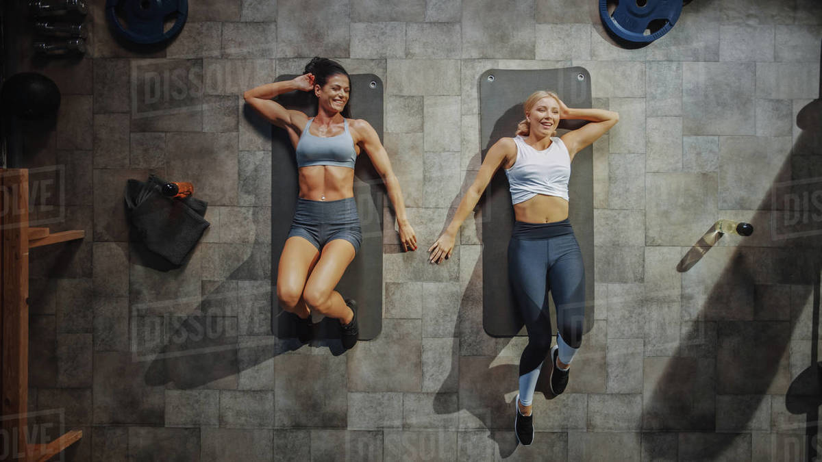 Two Professional Female Bodybuilders Doing Sit-up Exercises while Lying on the Yoga Mats in Hardcore Gym. Muscular and Athletic Beautiful Girls Muscle, Power and Cardio Workout. Royalty-free stock photo