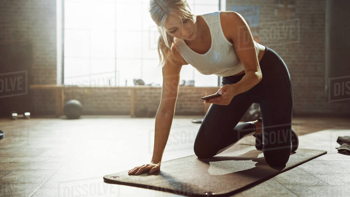 Beautiful and Young Girl Uses Smartphone App to Time Her Exercise on Fitness Mat. Gorgeous and Athletic Woman Does Mountain Climber Workout in Stylish Hardcore Gym Royalty-free stock photo