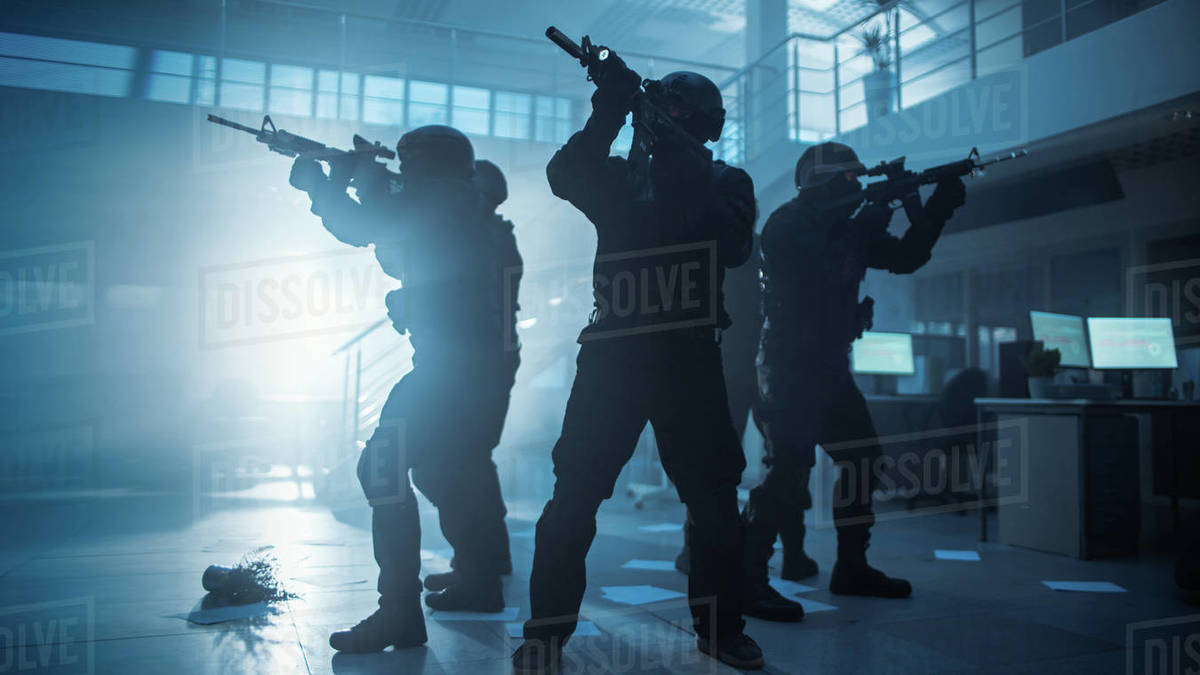 Masked Squad of Armed SWAT Police Officers in a Hall of a Dark Seized Office Building with Desks and Computers. Soldiers with Rifles and Flashlights Surveil and Cover Surroundings. Royalty-free stock photo