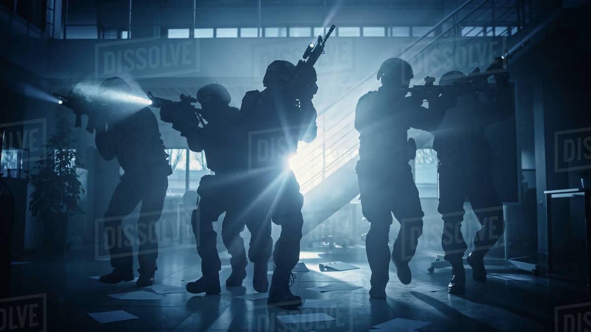 Masked Fireteam of Armed SWAT Police Officers Storm a Dark Seized Office Building with Desks and Computers. Soldiers with Rifles and Flashlights Move Forwards and Cover Surroundings. Royalty-free stock photo