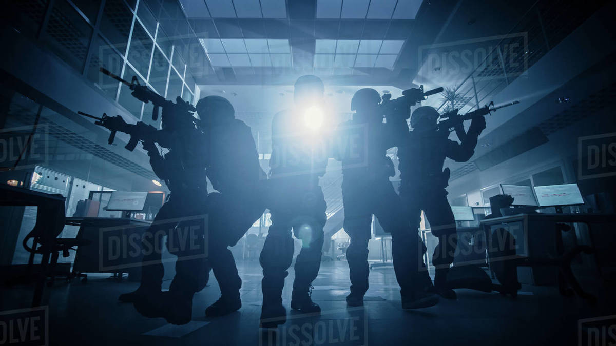 Masked Team of Armed SWAT Police Officers Move in a Hall of a Dark Seized Office Building with Desks and Computers. Soldiers with Rifles and Flashlights Surveil and Cover Surroundings. Low Angle Shot. Royalty-free stock photo