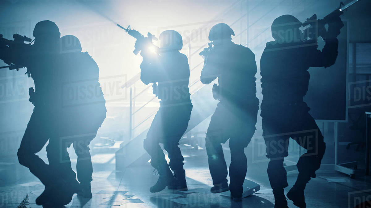 Masked Team of Armed SWAT Police Officers Move in a Hall of a Dark Seized Office Building with Desks and Computers. Soldiers with Rifles and Flashlights Surveil and Cover Surroundings. Royalty-free stock photo