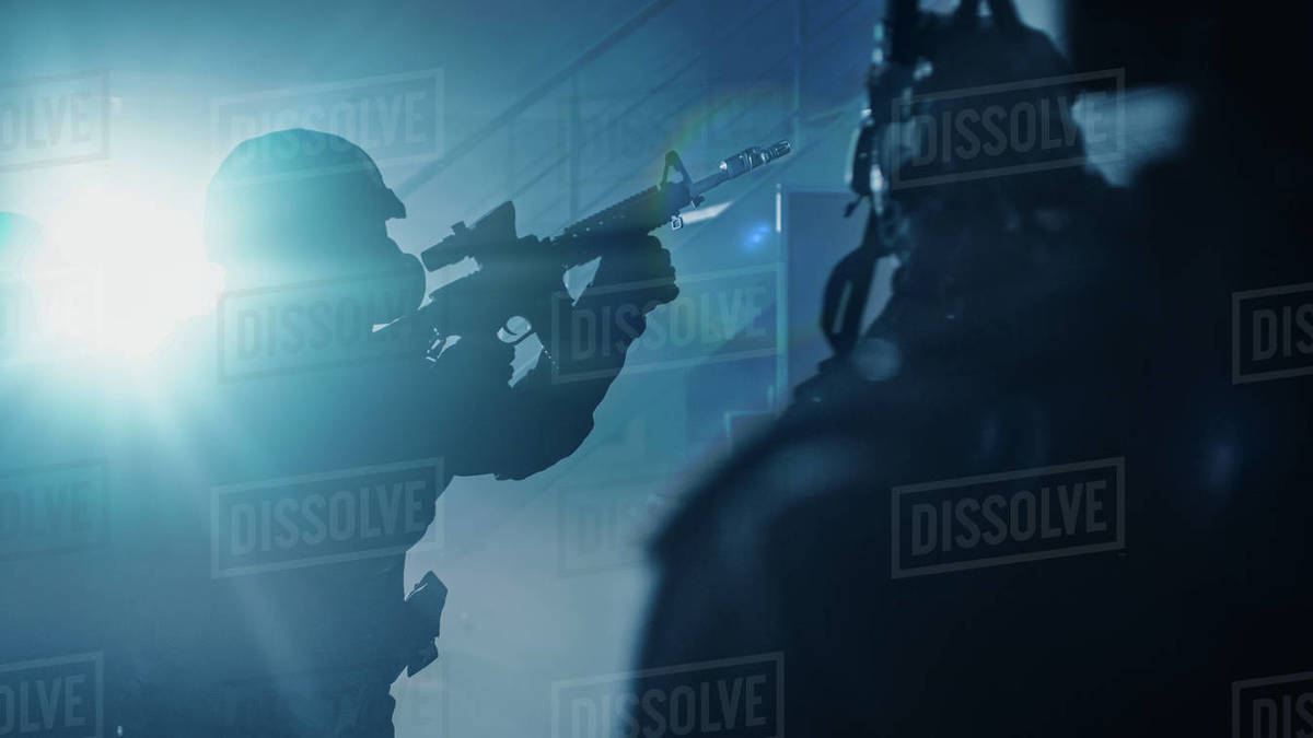Close Up Portraits of Masked Squad of Armed SWAT Police Officers Storm a Dark Seized Office Building with Desks and Computers. Soldiers with Rifles and Flashlights Move Forward and Cover Surroundings. Royalty-free stock photo