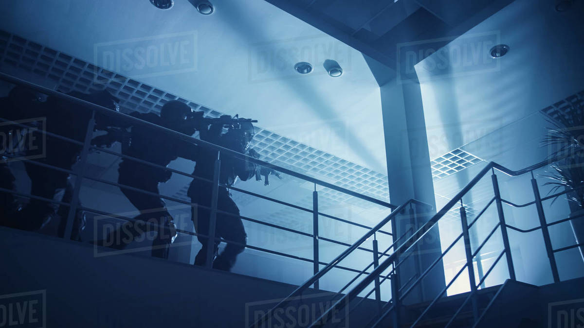 Masked Squad of Armed SWAT Police Officers Move in Formation on a Second Floor in a Dark Office Building. Soldiers with Rifles and Flashlights Move Forwards and Cover Surroundings. Below-view Camera. Royalty-free stock photo