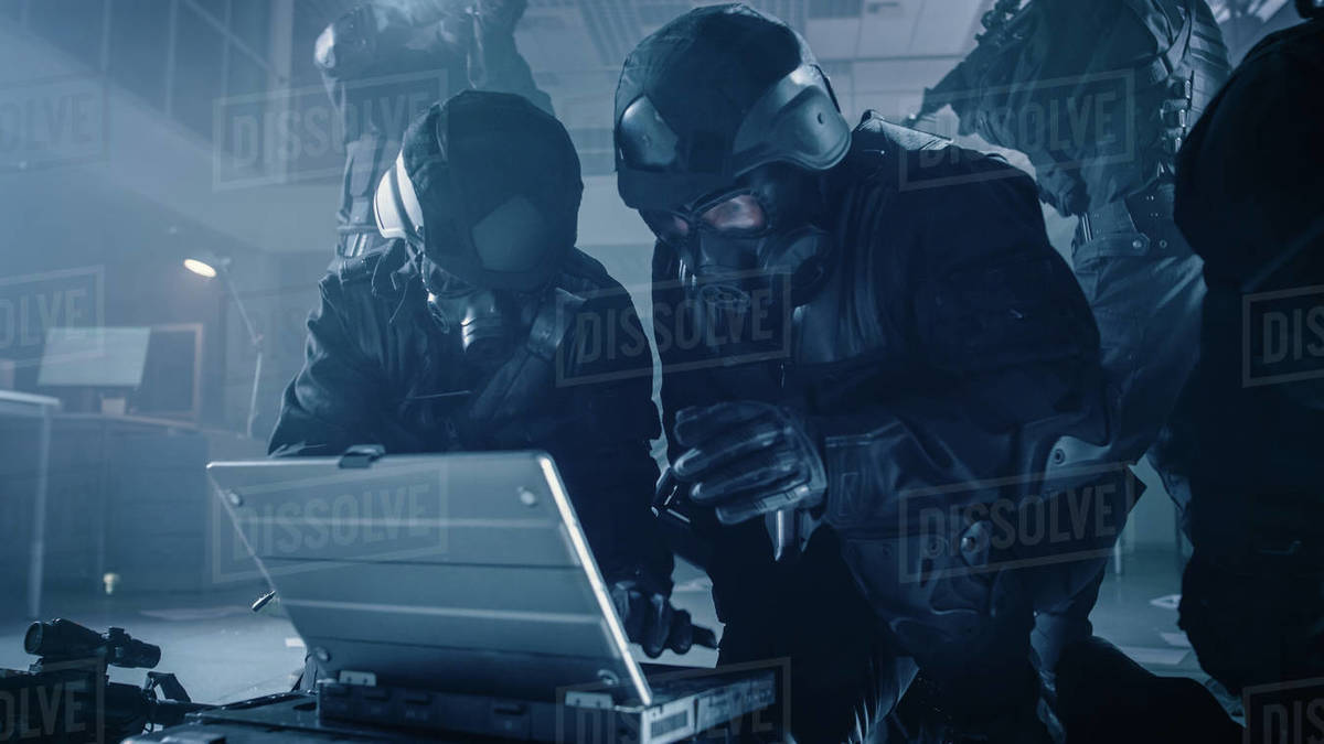 Masked Team of Armed SWAT Police Officers with Rifles are in Dark Seized Office Building with Desks and Computers. Soldier Opens a Laptop Computer to Plan a Tactical Attack. Royalty-free stock photo