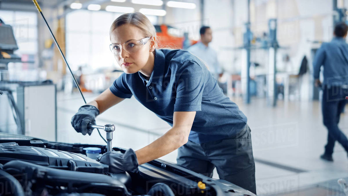 Beautiful Empowering Female Mechanic is Working on a Car in a Car Service. Woman in Safety Glasses is Fixing the Engine. She's Using a Ratchet. Modern Clean Workshop with Cars. Royalty-free stock photo
