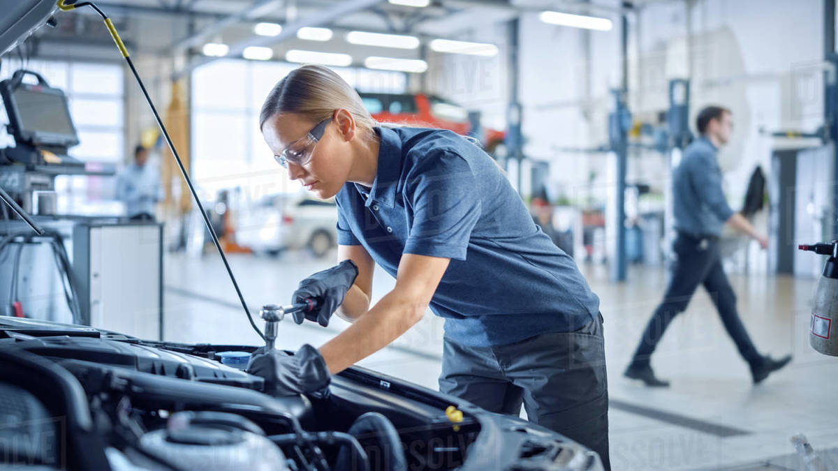 Beautiful Empowering Female Mechanic is Working on a Car in a Car Service. Woman in Safety Glasses is Working on an Usual Car Maintenance. She's Using a Ratchet. Modern Clean Workshop with Cars. Royalty-free stock photo