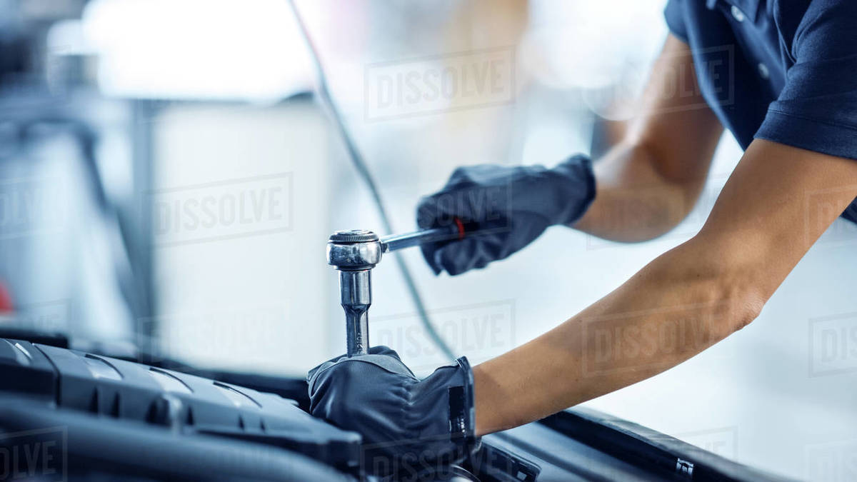 Close Up Shot of a Female Mechanic Working on a Car in a Car Service. Empowering Woman Makes an Usual Car Maintenance. She's Using a Ratchet. Modern Clean Workshop. Royalty-free stock photo