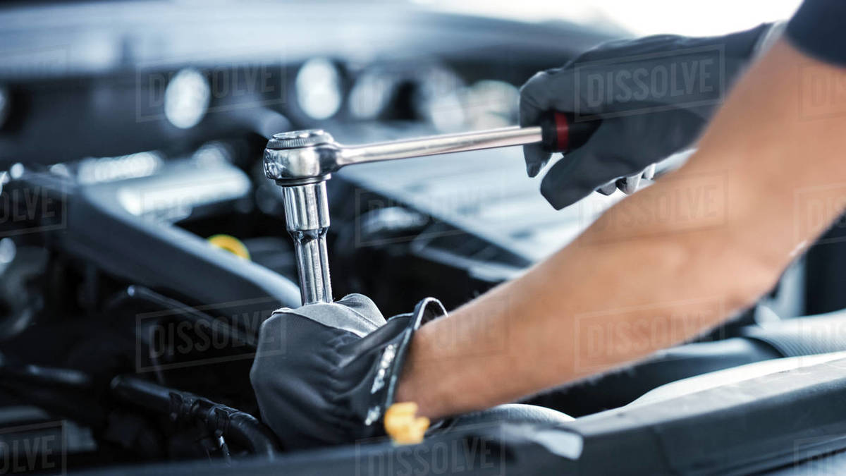 Close Up Shot of a Professional Mechanic Working on Vehicle in Car Service. Engine Specialist Fixing Motor. Repairman is Wearing Gloves and Using a Ratchet. Modern Clean Workshop. Royalty-free stock photo