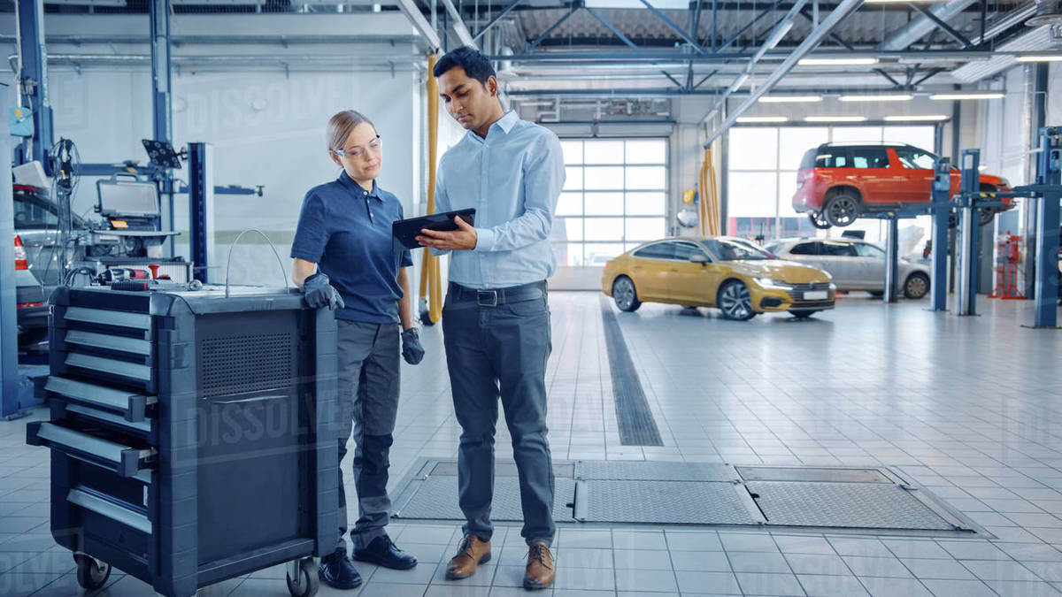 Car Service Manager and a Confident Female Mechanic Talk About Work Related Topics. They Use a Tablet Computer. Modern Clean Workshop with a Car on a Lift in the Background. Another Vehicle Drives In. Royalty-free stock photo