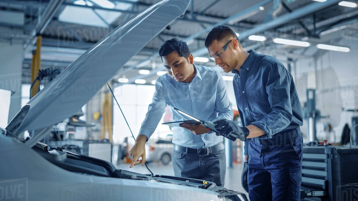 Manager Checks Diagnostics on a Tablet Computer and Explains the Engine Breakdown to a Mechanic. Car Service Employees Inspect Car's Engine Bay with a LED Lamp. Modern Clean Workshop. Royalty-free stock photo