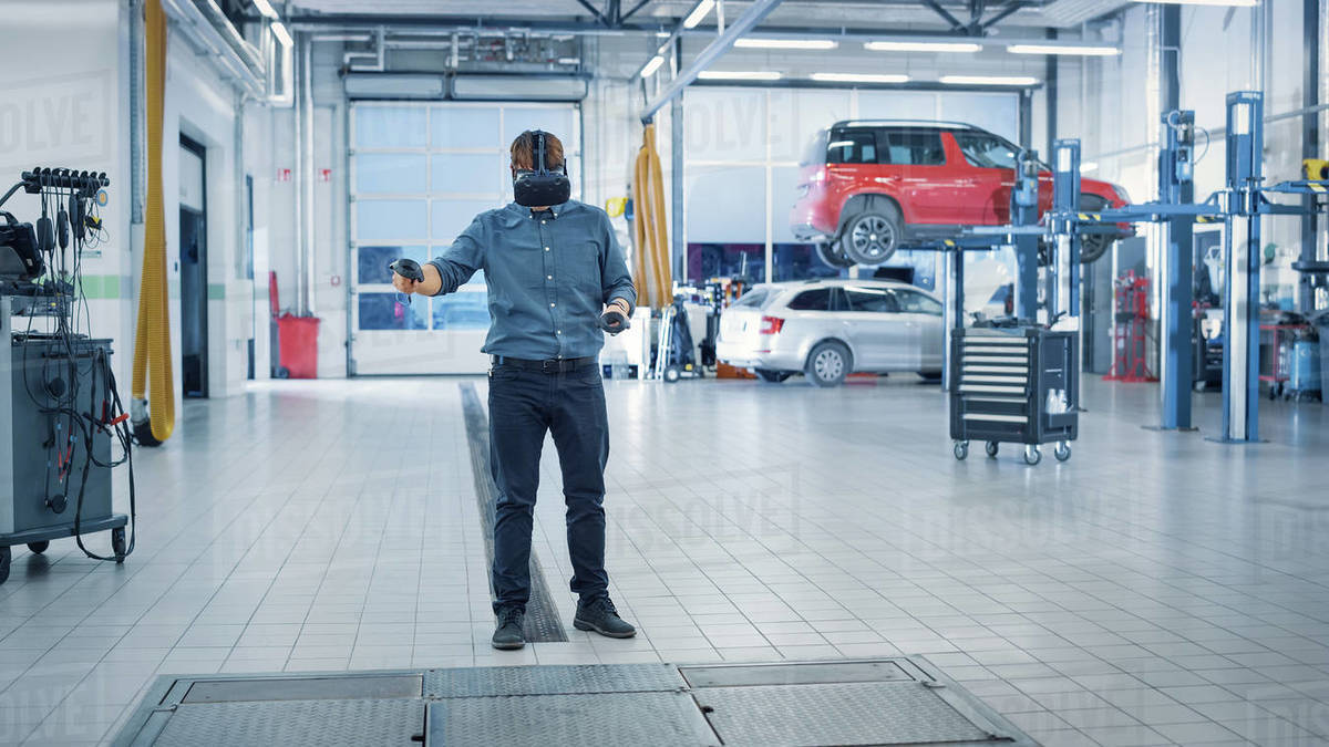 Specialist is Wearing a Virtual Reality Headset and Holding Two Joysticks in a Car Service. Mechanic is Investigating the Breakdown with the Help of Future Technology. Repairman in Modern Workshop. Royalty-free stock photo
