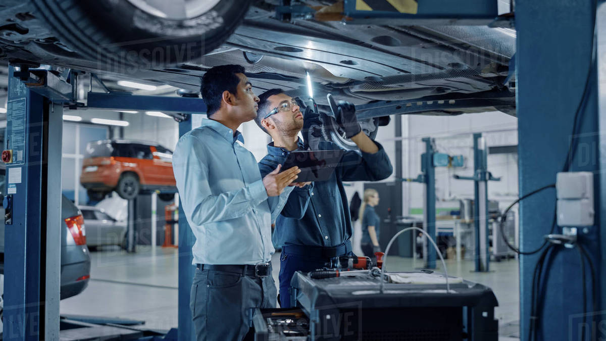 Manager Checks Data on a Tablet Computer and Explains the Breakdown to a Mechanic. Car Service Employees Inspect the Bottom of the Car with a LED Lamp. Modern Clean Workshop. Royalty-free stock photo