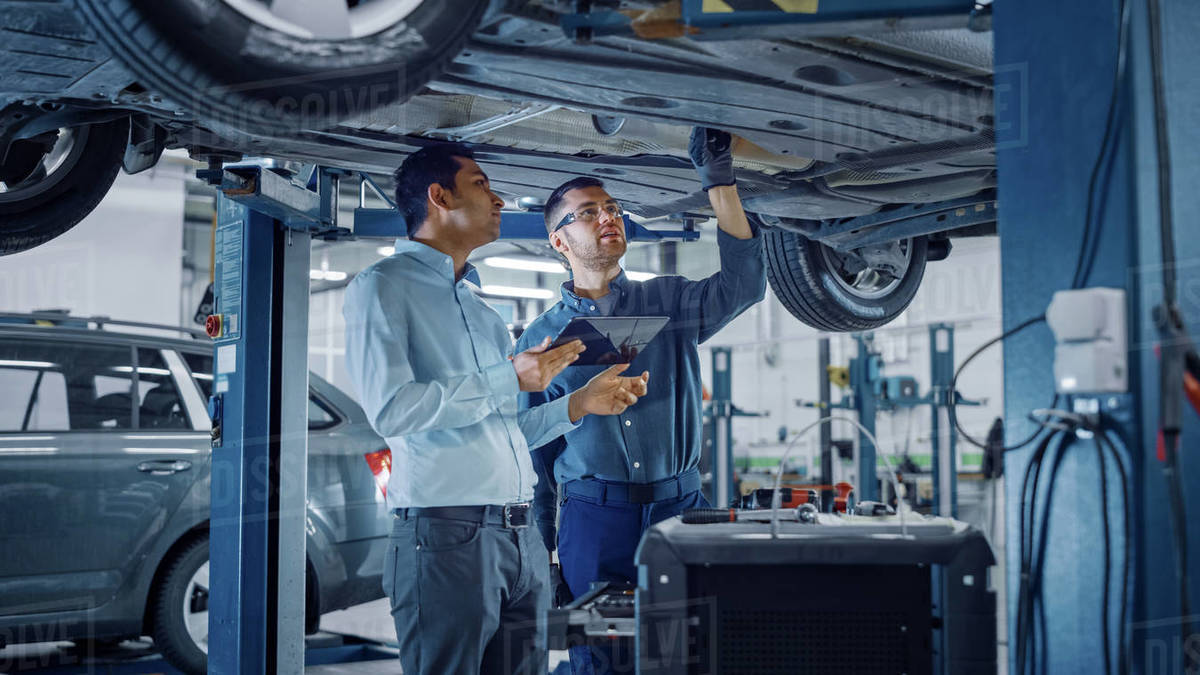 Manager Checks Data on a Tablet Computer and Explains the Breakdown to a Mechanic. Car Service Employees Inspect the Bottom and Skid Plates of the Car. Modern Clean Workshop. Royalty-free stock photo