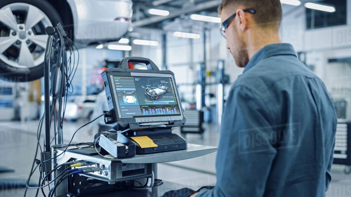 Car Service Manager or Mechanic is Running an Interactive Diagnostics Software on an Advanced Computer. Specialist Inspecting the Vehicle in Order to Find Broken Components and Errors in Data Logs. Royalty-free stock photo