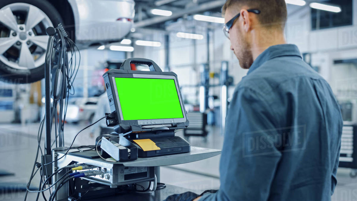 Car Service Mechanic is Running a Diagnostics Software on an Advanced Computer with Green Screen. Specialist Inspecting the Vehicle in Order to Find Broken Components and Errors in Data Logs. Royalty-free stock photo