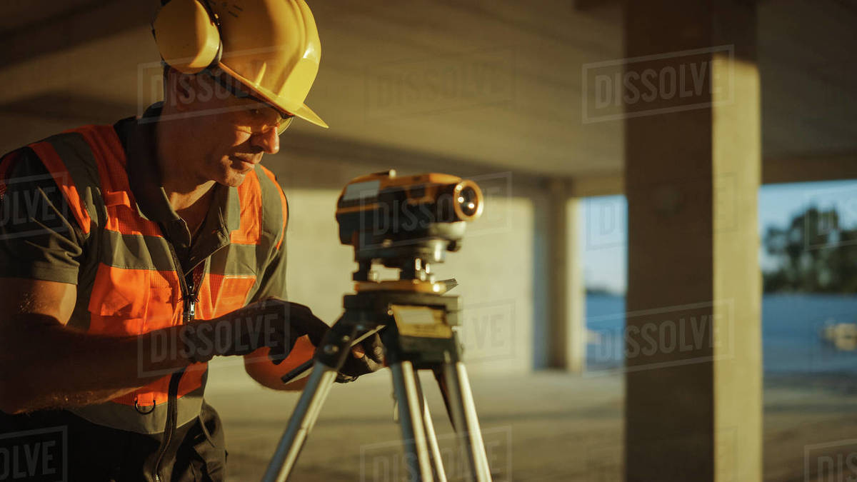 Inside of the Commercial / Industrial Building Construction Site: Professional Engineer Surveyor Takes Measures with Theodolite, Using Digital Tablet Computer. In the Background Skyscraper Formwork Frames and Crane Royalty-free stock photo