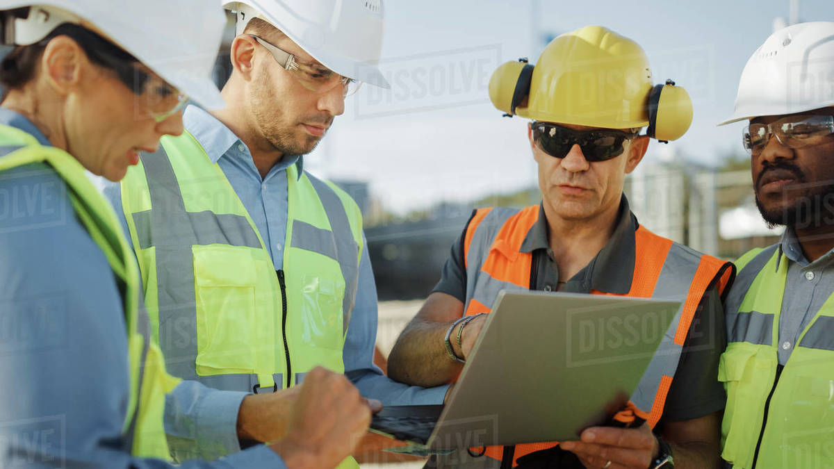 Diverse Team of Specialists Use Laptop Computer on Construction Site. Real Estate Building Project with Civil Engineer, Architectural Investor, Businesswoman and Worker Discussing Blueprint Plan Royalty-free stock photo