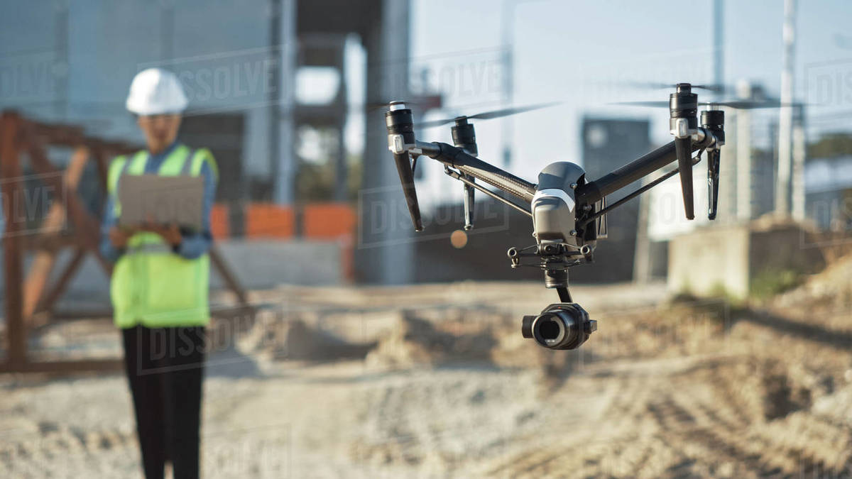 Specialist Controlling Drone on Construction Site. Architectural Engineer or Inspector Fly Drone on Building Construction Site Controlling Quality. Focus on Drone Royalty-free stock photo